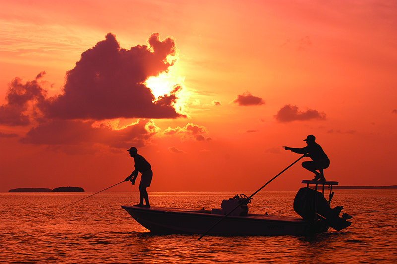 As the sun sets, a Florida Keys bonefish guide, right. points his angler to a bonefish on fly tackle off Islamorada in the  Florida Keys. More than 200 International Game Fish Association saltwater world records have been set in the Florida Keys. (Photo by Bob Krist/Florida Keys News Bureau)